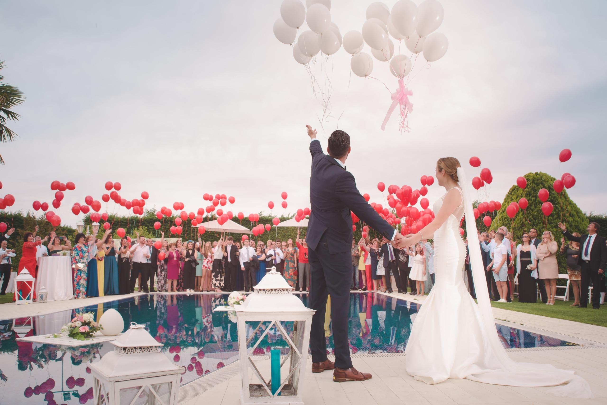 Mariés de dos face à une piscine ou se trouvent les invités à l'opposé pour un lâcher de ballons