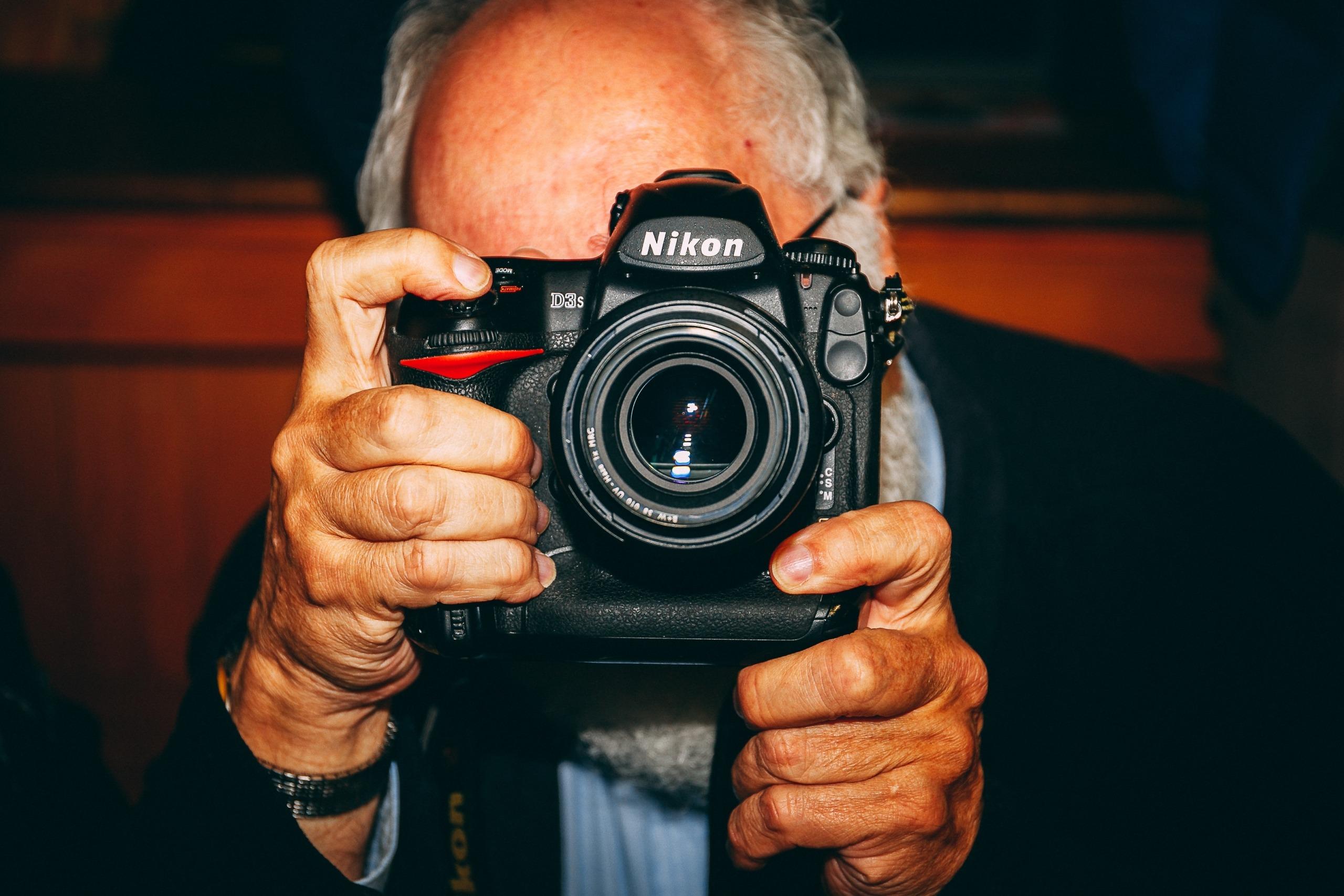 vidéaste homme d'un certain âge qui tient un appareil photo pour filmer une cérémonie de mariage